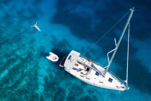 yacht and swimming woman and clear water - caribbean paradise